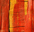 Old crumbling wooden surface covered with red paint lit by sunlight closeup Stock Photos