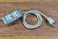 Old damage extension cord on wood background Royalty Free Stock Photo
