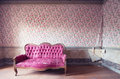 Old damaged red couch in an antique house flowers wallpaper in the wall Stock Photography