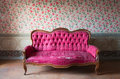 Old damaged red couch in an antique house flowers wallpaper in the wall Stock Images