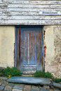 Old decayed wood door rotten in a house with flaked painting and cracked plaster on brick wall in stavanger Royalty Free Stock Photography