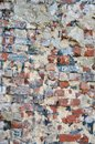 Old decaying brick wall with repairs and crumbling cement layer Royalty Free Stock Photo