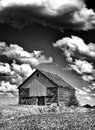 Old desolate barn with storm clouds overhead spooky haunted like you would see on halloween in black and white Stock Images