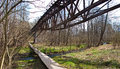 Old desolate bridge and bike path panorama of an steel unused in forest with wooden natural over a creek poland polanow Royalty Free Stock Photography