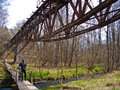 Old desolate bridge and bike path panorama of an steel unused in forest with wooden natural over a creek poland polanow cyclist Royalty Free Stock Photography