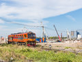 Old diesel electric locomotive is passing the construction site near the urban station Royalty Free Stock Image