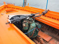 Old diesel engine in wooden boat fishing caique clinker with freshly marine painted bright orange deck greek fishing village Stock Images