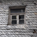 Old dilapidated house covered with slate roof and worn skylight Royalty Free Stock Photography