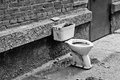 Old dirty toilet in the yard. Black and white Royalty Free Stock Image