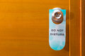 Old Do Not Disturb sign tag haning on metal door knob, concept o Royalty Free Stock Photo