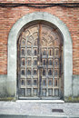 Old doorway traditional wooden ornamental door romanesque style on the main street Royalty Free Stock Images