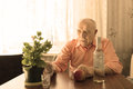 Old drinking man looking at plant on the table bald green as pot placed wooden with apple shot glasses and vodka bottle Stock Photos