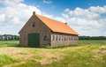 Old dutch barn of brick masonry with an orange tile roof in a rural landscape a blue sky white clouds in summer Stock Photography