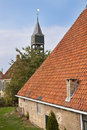 Old dutch farmhouse with churchtower behind it Stock Photo