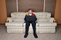 Old elderly senior man using laptop computer portrait of an sitting on a couch or sofa in his house note the colorful sweater Royalty Free Stock Photo