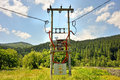 Old electric generator power line with device attached near the fir forest Stock Photos