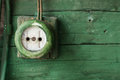 Old electric outlet on green wooden wall Royalty Free Stock Photo
