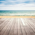 Old empty wooden pier perspective on sandy beach with and sea a background Royalty Free Stock Image