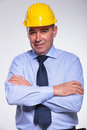 Old engineer stands with hands folded senior standing his while smiling at the camera on gray background Stock Photography