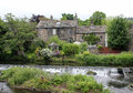 Old english riverside home a quaint alongside the river aire with a man made industrial waterfall photo taken in bingley yorkshire Stock Photography