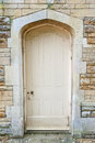 Old external door in a stone wall weathered exterior set buff coloured Royalty Free Stock Image