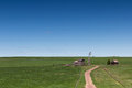 Old farm with a barn and a windmill in the green, grassy field under a blue sky Royalty Free Stock Photo