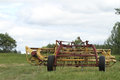 Old farm implement in a meadow yellow and red with tires Stock Photography