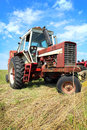 Old farm tractor in grass field an getting ready to bail a Stock Photography