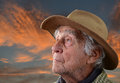 Old farmer against sunset senior man wearing a tan felt hat with a sparse beard on a background of blue and orange Stock Photo
