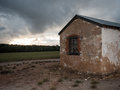 Old farmhouse building at dusk eerie under a stormy sky Royalty Free Stock Image