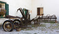 Old farming tools and vehicles outside a country house Royalty Free Stock Images