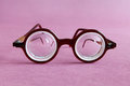 Old fashion design spectacles eyeglasses on pink violet paper background. Vintage style men fashion accessories for Royalty Free Stock Photo