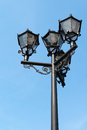 Old fashion street lamp with modern lighting system against a bright blue sky background Stock Photo