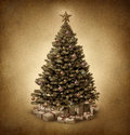 Old fashioned christmas tree on vintage parchment paper grunge texture with traditional ornate decorative balls and gifts with Stock Photo