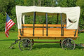 Old fashioned horse drawn covered wagon with an american fkag Royalty Free Stock Photos
