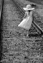 Old fashioned little girl walking on a rail road track beautiful in an white dress and straw hat walks along an Stock Photos