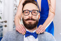 Old fashioned man with a beard and curled mustache woman manicure straightens bow tie to in glasses photo toned in sepia Royalty Free Stock Images