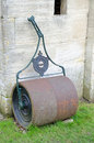 Old fashioned metal lawn roller against stone wall Royalty Free Stock Images