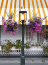 Old fashioned street lamp gas decorated with summer flowers and american flags in front of a victorian porch and a yellow and Royalty Free Stock Image