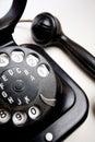 Old fashioned telephone on the white backing under strange angel isolated Royalty Free Stock Photo