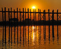 An old figure crossing the u bein bridge at sunset amarapura myanmar burma wearing a rice hat Royalty Free Stock Images