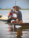 An old fisherman on inle lake myanmar smiling using his leg to hold down a fishing trap in burma Royalty Free Stock Image
