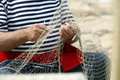 Old fisherman mending nets an sits his fishing net Stock Image