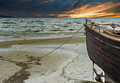 Old fishing boat at the baltic sea kurzeme latvia sunrise on sandy beach of europe Royalty Free Stock Photo