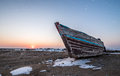 Old fishing boat at sunset time in winter Royalty Free Stock Photo