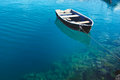 Old fishing boat on the transparent water surface Stock Images