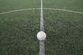 Old football at kick off mark on fake grass Royalty Free Stock Photo