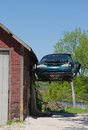 Old ford mustang hanging from garage beat up in the air off the side of a Stock Photo