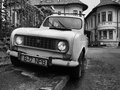 Old french car black and white picture with an downtown in bucharest romania Royalty Free Stock Photos
