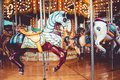 Old French carousel in a holiday park. Three horses and airplane on a traditional fairground vintage carousel. Merry-go-round with Royalty Free Stock Photo